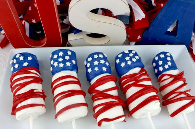 Red white and blue marshmallow pops on a plate.