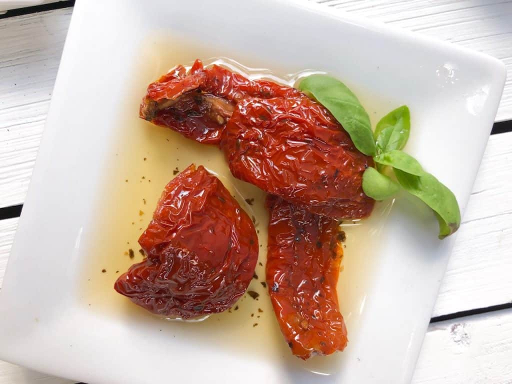 Sun dried tomatoes on a white plate.