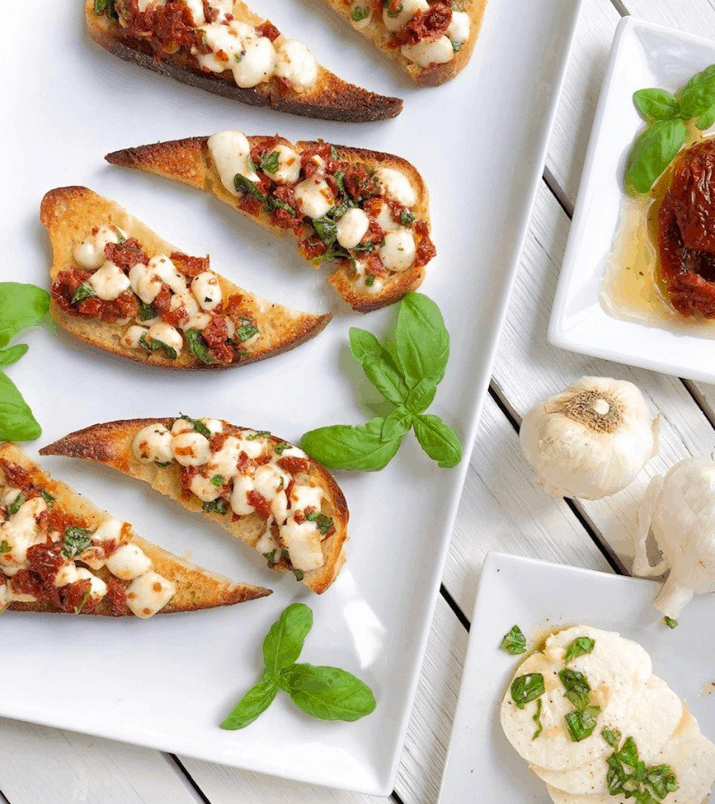 party appetizer bruschette on a plate with basil and garlic