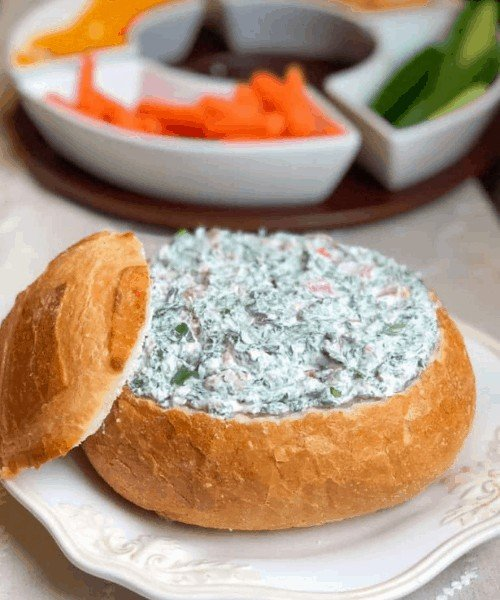 spinach dip in a bread bowl with veggies in background