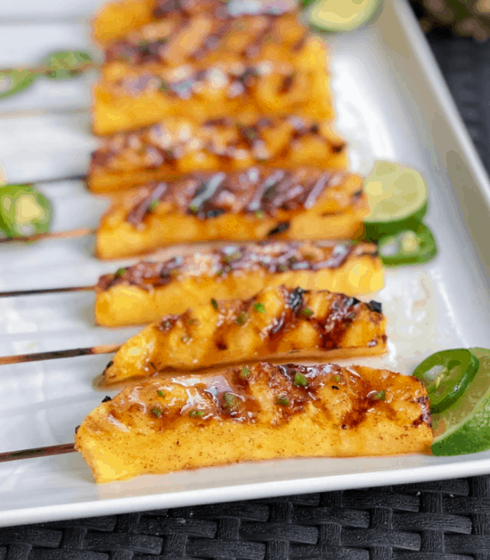 Grilled pineapple wedges skewered on a plate.
