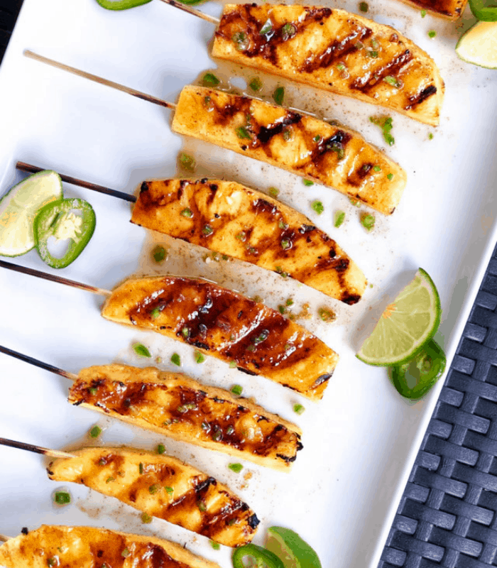 Grilled pineapple skewers on a white plate with limes