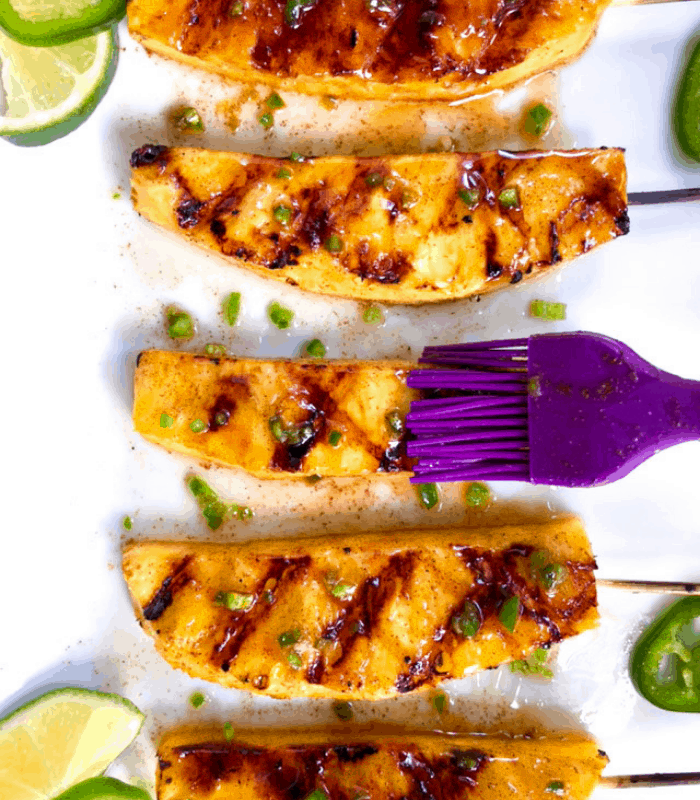 Brushing grilled pineapple with honey lime glaze.