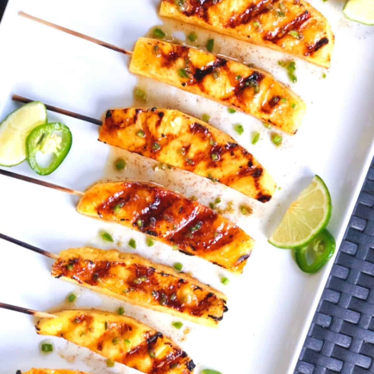 Grilled pineapple spears on a plate.
