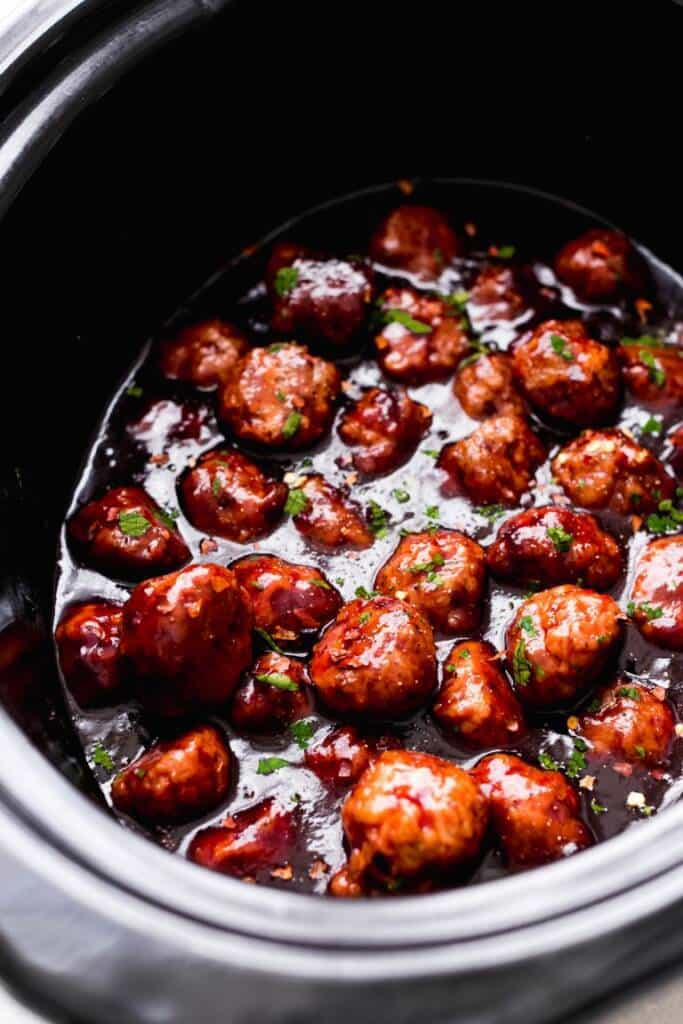 football meatballs in a crock pot sitting in a sweet spicy sauce.