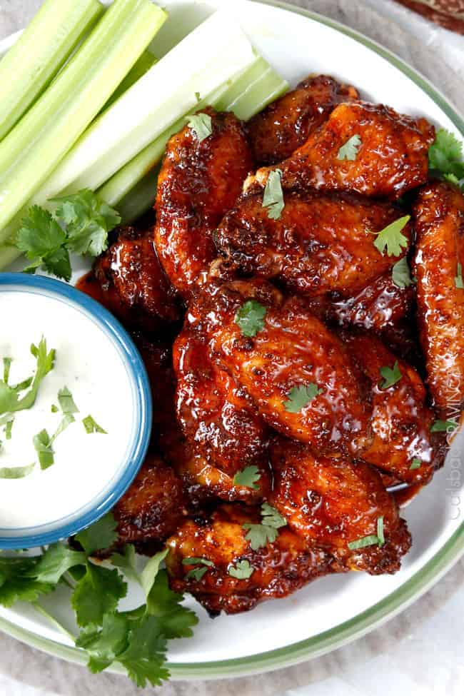 chicken wings smothered in sauce with ranch on the side.