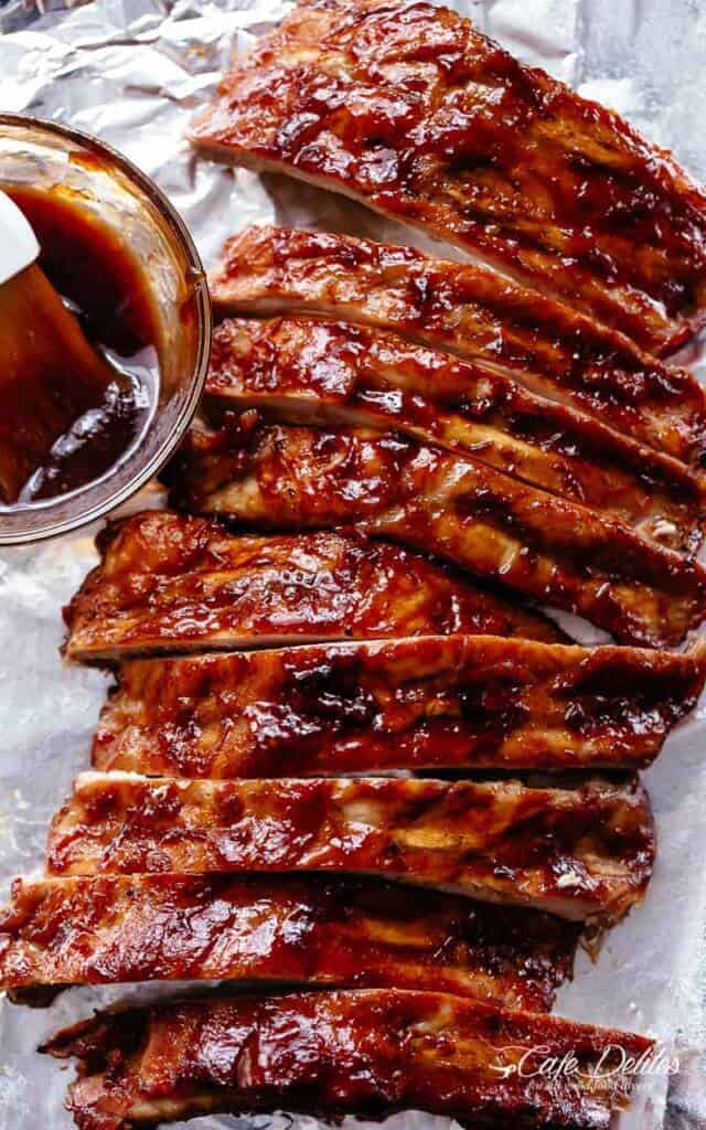 Slow cooker ribs slathered in a bbq sauce over tin foil.