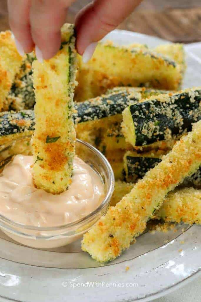 crispy zucchini sticks being dipped into sauce.