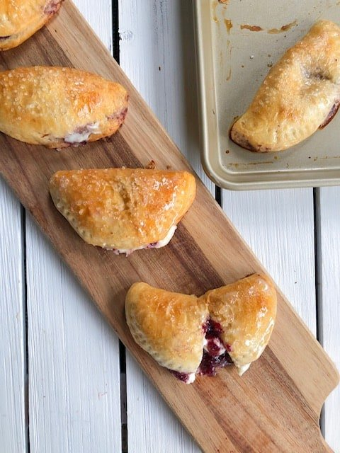 Homemade baked sweet empanadas stuffed with a cherry cream cheese filling! They are a fun dessert to enjoy any time of year!