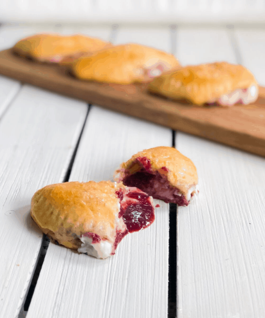 dessert empanadas on a cutting board with one cut in half with filling spilling out.