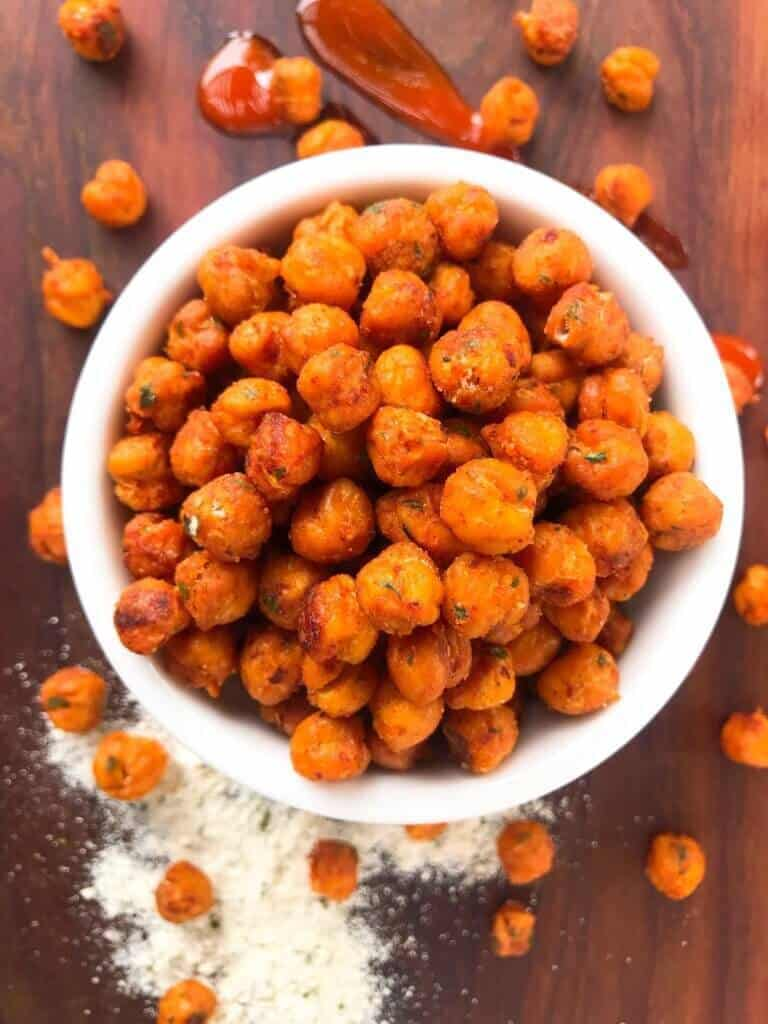 Roasted chickpeas in a white bowl covered in buffalo sauce.