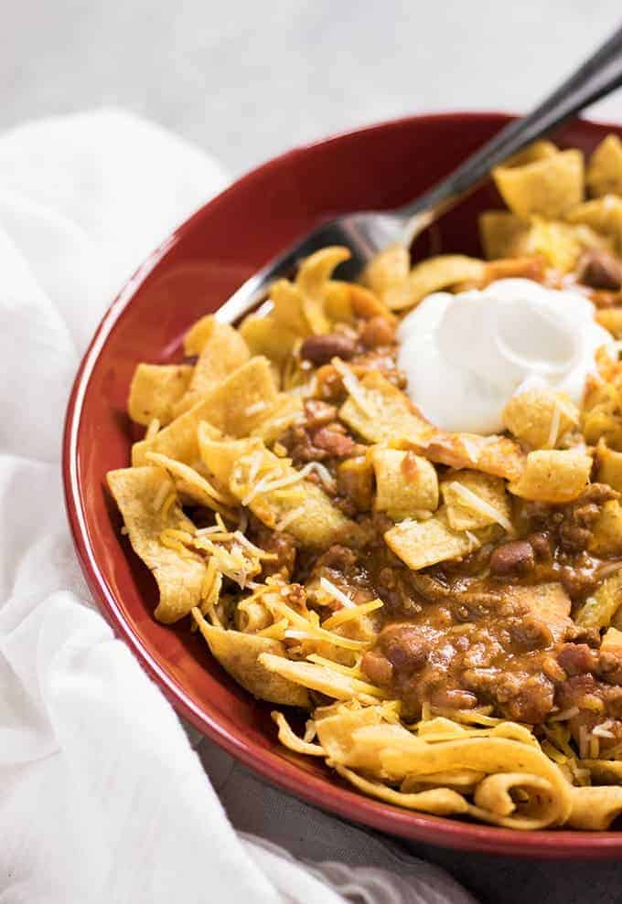 corn chips topped with chili and sour cream in a bowl.