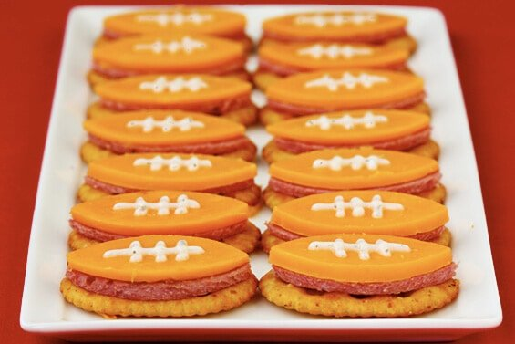 cheese cut into shapes of football and served over a crackers with sausage.