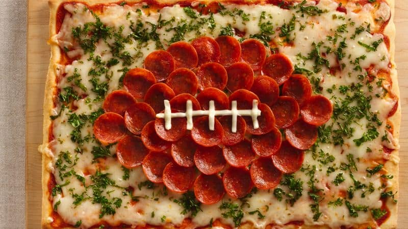 square pizza on a table with pepperoni slices formed into a football and cheese for the laces.