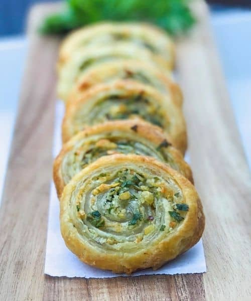 Puff pastry herb pinwheels appetizer on a wooden plank
