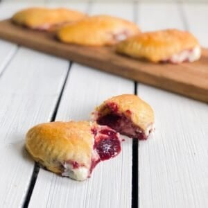 sweet empanadas with cherry filling on white board cut open