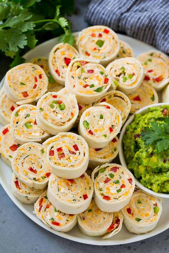 tortilla wraps spread onto a platter with guacamole on the side.