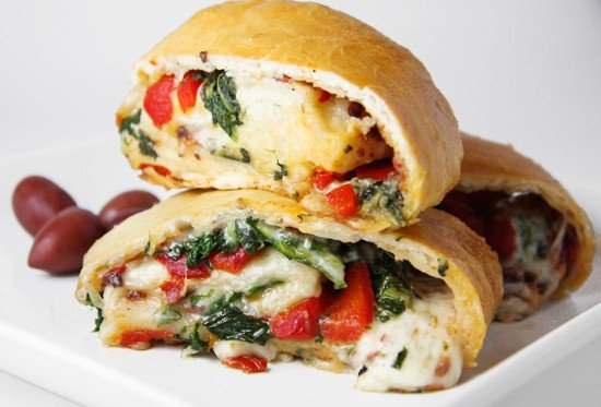 veggie stromboli cut in half with red peppers spinach and cheese oozing out.