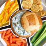 Overhead shot of cold spinach dip in a breadbowl with veggies.