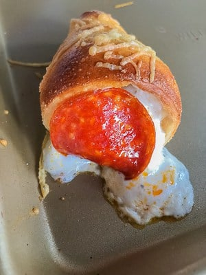Pizza cone on baking sheet with cheese oozing out.