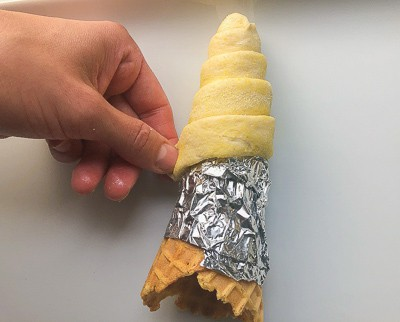 Showing how to wrap cone with pizza dough.
