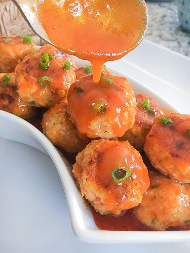 Buffalo sauce turkey meatballs in a bowl with sauce over top.