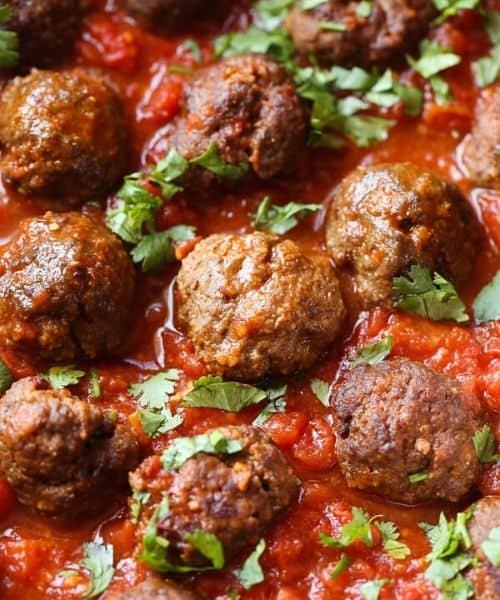 Meatballs sitting inside a red sauce in a crock pot.