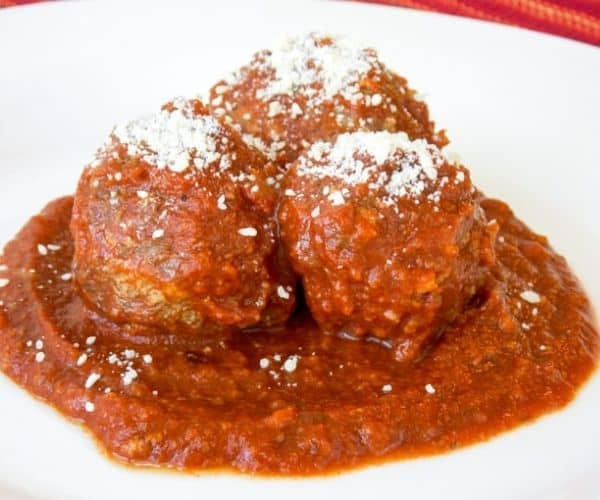 Three meatballs on a plate topped with Parmesan cheese.