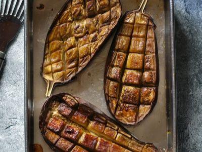Scored roasted eggplant on a baking sheet.