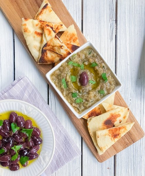 Greek roasted eggplant spread in a bowl with pita and olives.