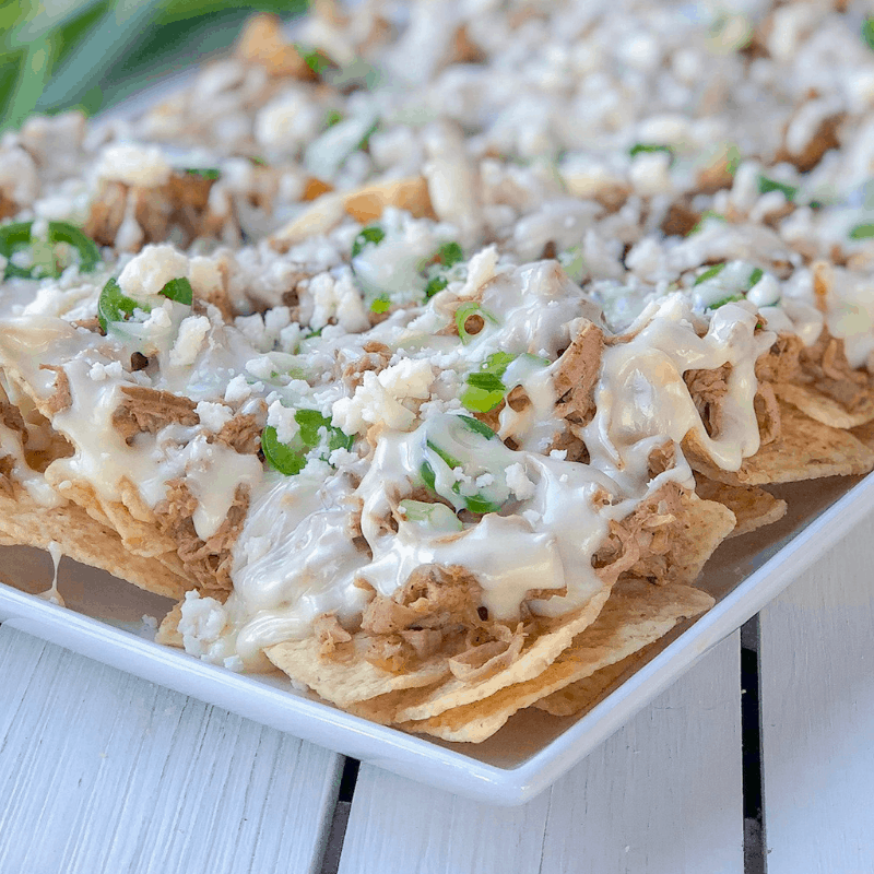 Pulled slow cooker pork nachos topped with melted cheese.