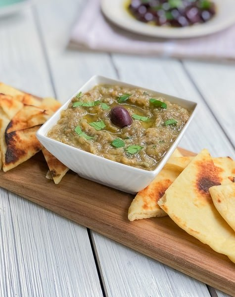 eggplant dip in a white bowl on cutting board with pita triangles for party serving