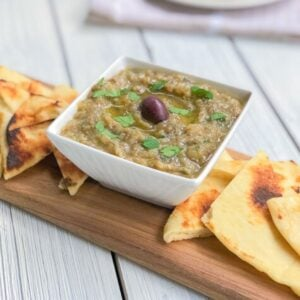 Eggplant dip in a bowl with pita triangles on the side.