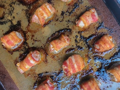 Baked pork wrapped bacon on a baking sheet.