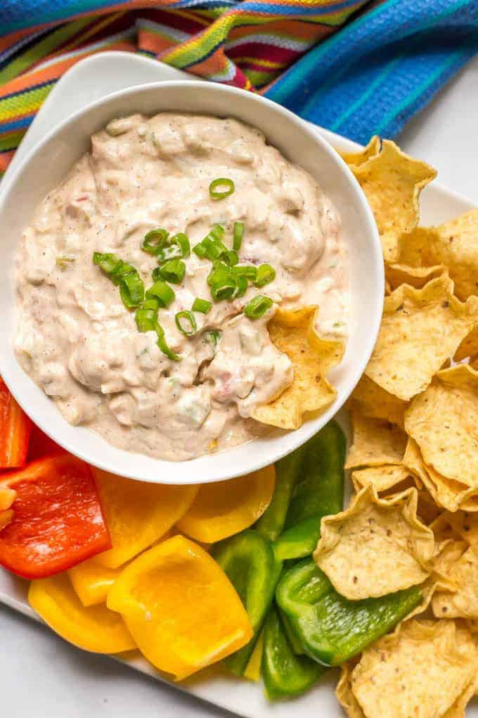 Cheese dip with cold chili and chips on the side.