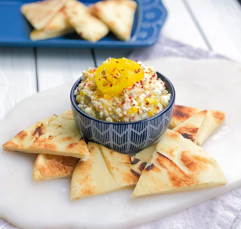 Feta cheese in a bowl with banana peppers on top with pita around it.