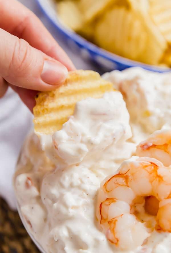 Potato chip dipping into a shrimp dip.