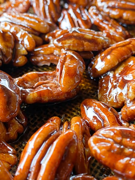 Shiny glazed pecans on a nonstick sheet.