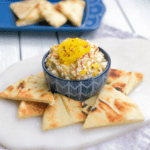 feta cheese dip in a bowl with pita bread