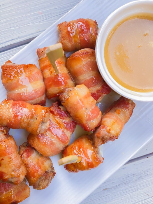 Pork bites wrapped in bacon with dipping sauce on the side.