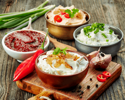 Four dips on a table with peppers and scallions on table.