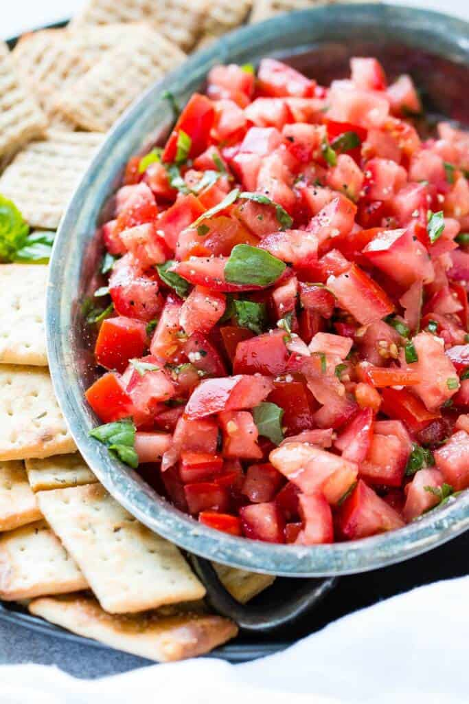 Chopped tomatoes with basil in a bowl with crackers on the side.