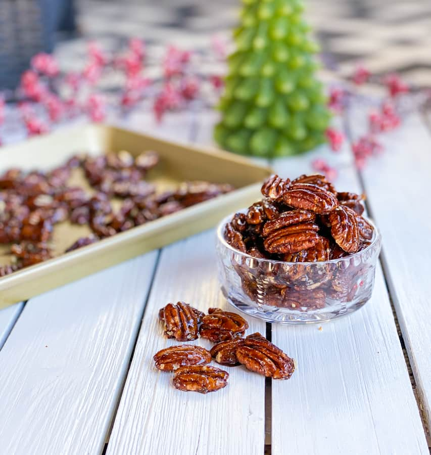 Candied pecans on a table with Christmas tree in the background.