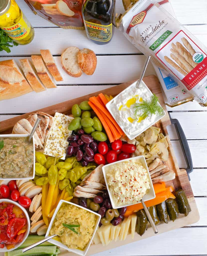Greek party finger food spread with small plates, dips, veggies and breadsticks