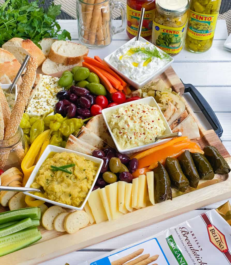 Large Greek meze board with dips, spreads, veggies and bread.