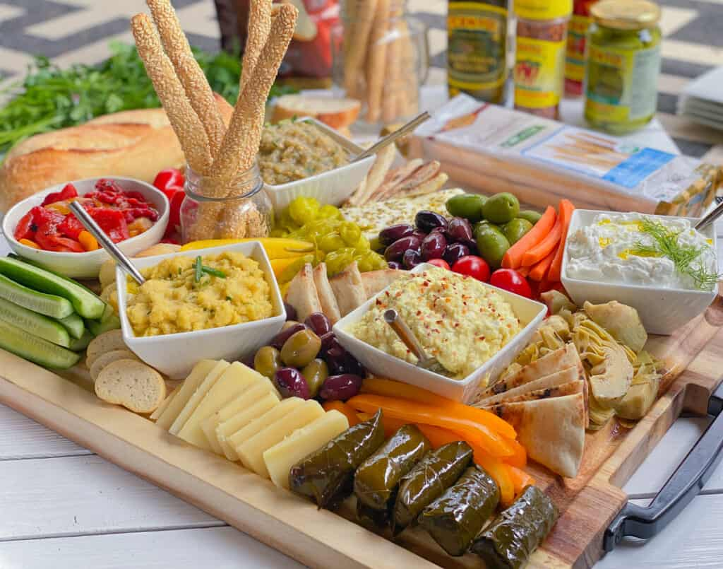 Greek meze appetizer board with dips and spread on a large wooden cutting board.