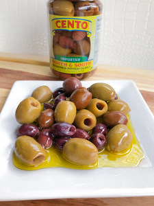 Cento jar of olives on a plate.