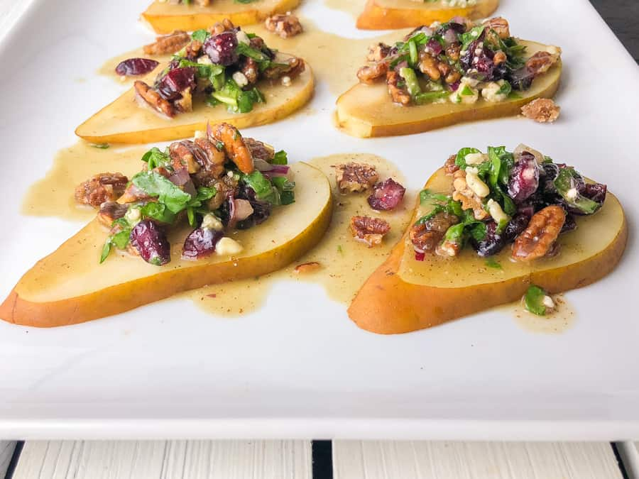 slices of pears on a plate topped with cheese and craisin salad