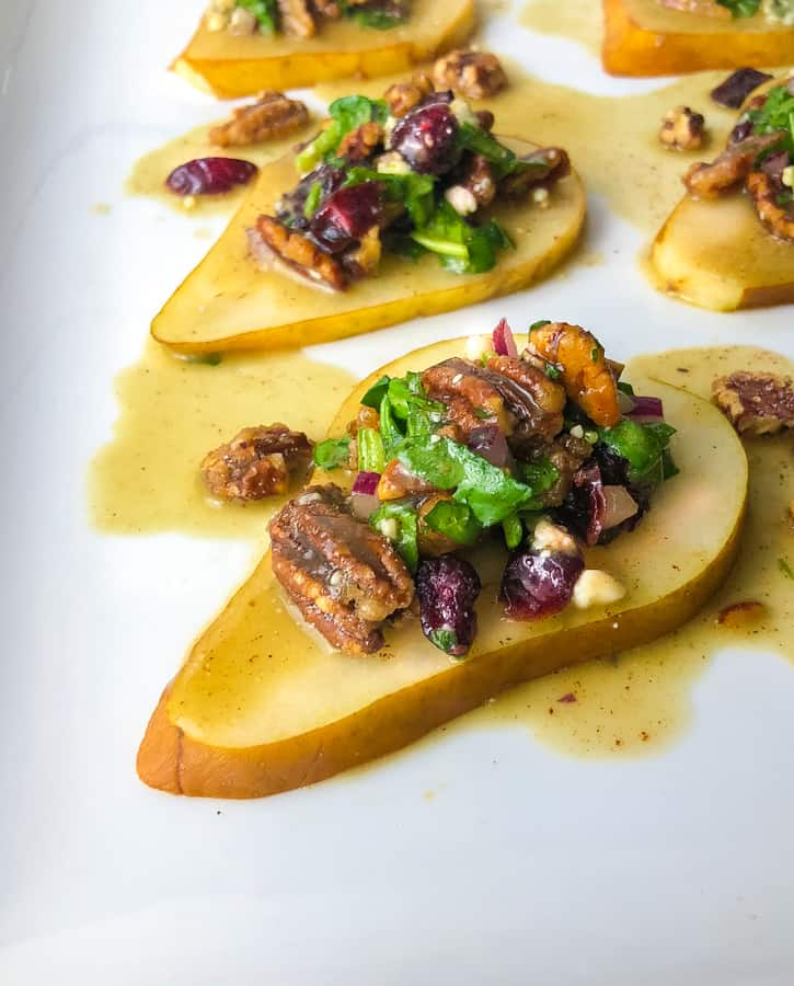 pear slices on a plate topped with pecans cheese and dressing