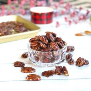 Candied pecans in a clear bowl on a table.